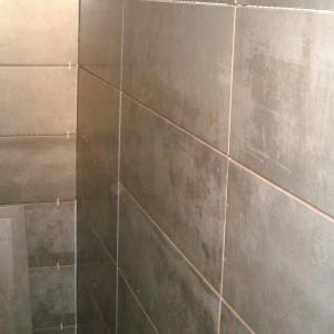 Flislegging på vegg med grå fliser.
