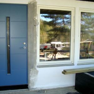 Ny blå ytterdør og nye hvite vinduer sett fra utsiden.