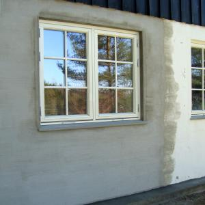 Nytt hvitt vindu i soverom sett fra utsiden, likt eksisterende vinduer i kjelleren. Pusset murvegg.