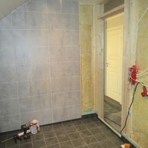 Fliser lagt på gulv og montering av Berry Alloc våtromsplater på vegg i baderom.