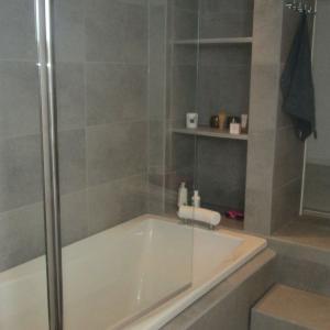 Badekar har dusjvegger og plassbygget hylle.