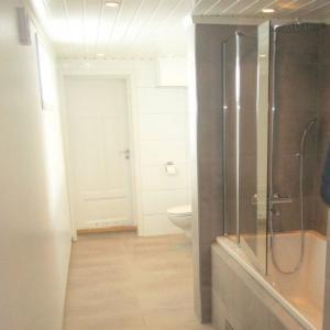Ferdig baderom med badekar, dusjvegger, vegghengt WC, vask og speil. Fliser på gulv og enkelte vegger. Våtromsplater på andre vegger.