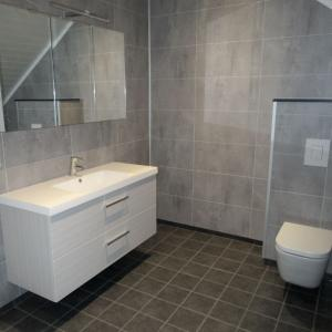 Ferdig baderom med flislagt gulv, Berry Alloc våtromsplater på vegg, vegghengt WC, vask og speil.