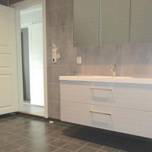 Ferdig baderom med flislagt gulv, Berry Alloc våtromsplater på vegg, ny innerdør, vask og speil.