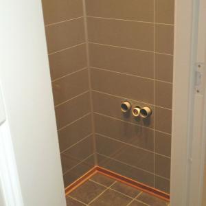 WC-rom: ferdig flislagt gulv og nye Berry-Alloc plater på vegger. Rør til servant stikker ut av veggen.