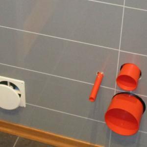 WC-rom: ferdig flislagt gulv og nye Berry-Alloc plater på vegger. Rør til vegghengt WC stikker ut av veggen.