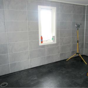 Mørk grått belegg montert på gulv, BerryAlloc våtromsplater med flismønster montert på vegger. Ferdig listet rundt vindu med hvitmat listverk.