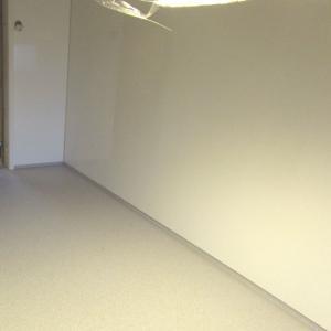 Kjøkkenrom med glatte hvite plater på alle vegger. Mot gulv med belegg.