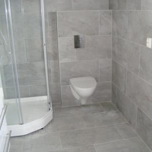 Ferdig bad, med dusjkabinett og vegghengt klosett. Grå fliser på vegg og gulv.